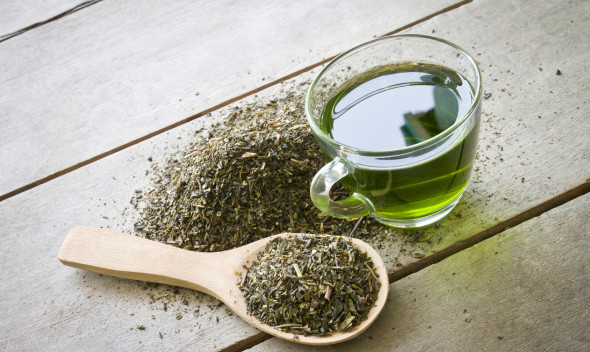 cup of green tea and spoon of dried green tea leaves on wooden background